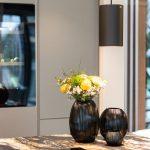 Offener Wohn Essbereich mit Küche Kochinsel Vasen Blumen Schwarz Marmor