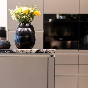 Offener Wohn Essbereich mit Küche Arbeitsplatte Granit Glasfronten Taupe Grau Schwarz Vasen Blumen Backofen