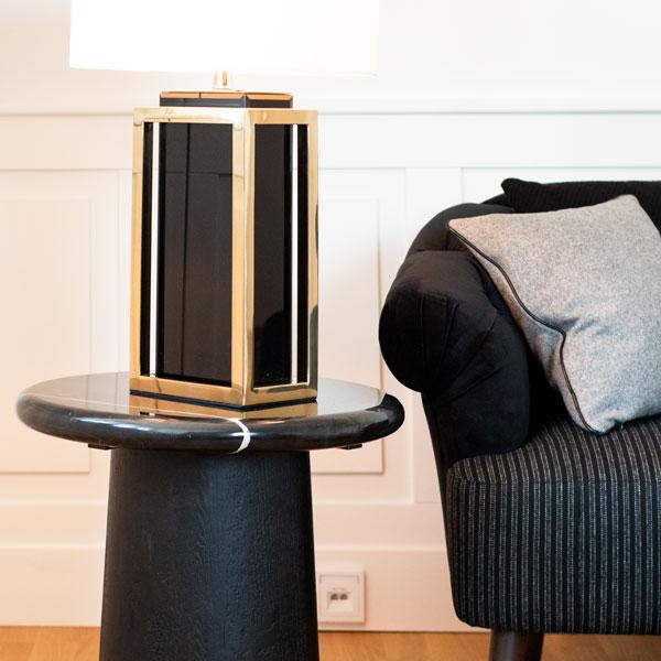 Wohnzimmer Einrichtungskonzept schwarzer Beistelltisch Schwarze Couch Sofa graues Kissen Tischleuchte