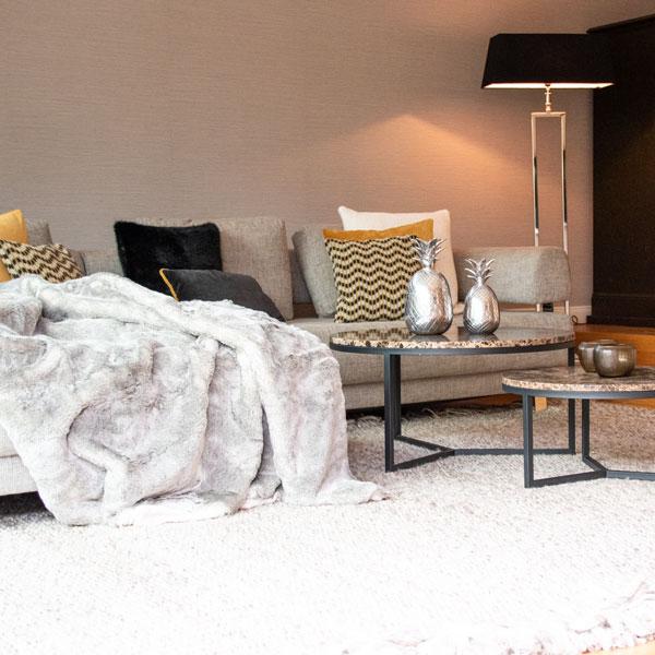 Wohnen mit Kamin Lounge Felldecke Stehleuchte Beleuchtung Wohnen Couch mit Kissen dekorieren Teppich Wohnzimmer gestalten