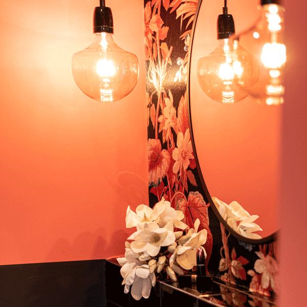 Interior Design Badezimmer Inspiration orangenes Bad florale Tapete runder Spiegel Blumen