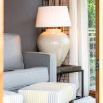 Graues Sofa schwarzer Beistelltisch große Leuchte gestreifte Poufs Inneneinrichtung Ideen Einrichtungsideen Kundenprojekt Einrichtungskonzept Interior Design Räume planen