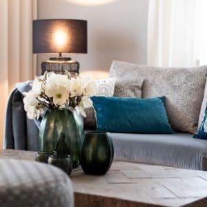 Wohnzimmer blaues Kissen Guaxs Vase Leuchte Blumendekoration Couchtisch Inneneinrichtung Ideen Einrichtungsideen Kundenprojekt Einrichtungskonzept Interior Design Räume planen