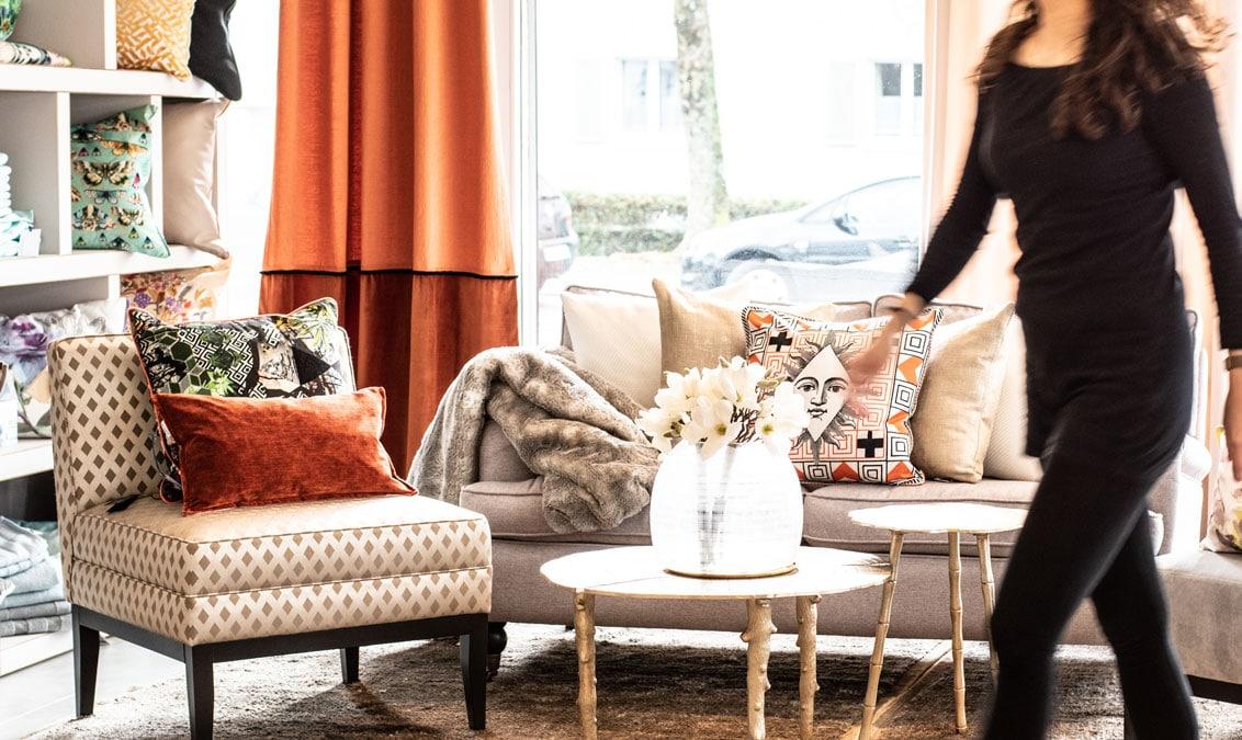 Showroom Einrichtungskonzept Wohnzimmer Kissendekoration auf Sofa Beistelltisch Blumendekoration Vasen roter Vorhang